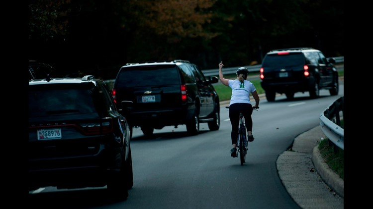 Woman who flipped the bird at Trump motorcade sues over forced resignation