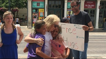 Family and friends offer free hugs in front of the Alamo after weekend's mass shootings